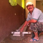 Juan applying the tile on the floor of church