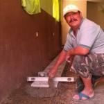 Juan applying the tile on the floor of church